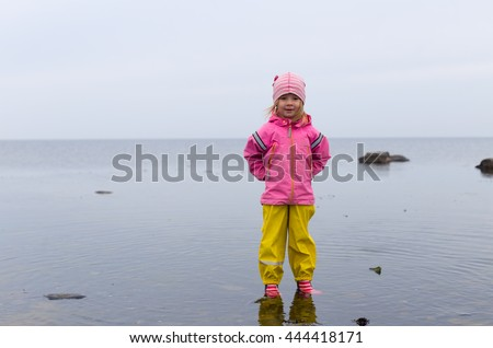 small blond girl in preschool age playing in water on north of europe, wearing rain and gummy clothing on cloudy day walking in shallow sea water