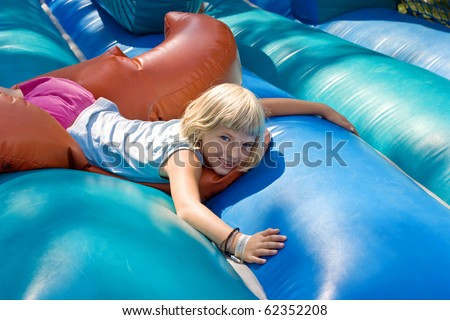 Small blonde girl lying on a inflatable blow-up toy for kid.