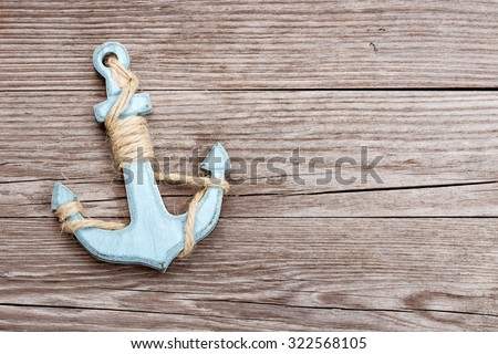 small blue anchor on a wooden background - stock photo