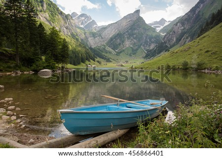 Small blue boat on an alpine lake, high mountains around covered with snow reflecting in the lake surface - stock photo