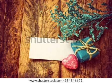small blue gift box, pink heart, branch decor, empty tag on old rough floor boards - stock photo