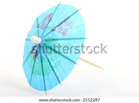 Small blue paper umbrella for alcoholic drinks, macro close up with copy space - stock photo