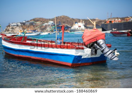Small blue, red and white boat in the port of Santa Marta in Colombia, view of blurred cranes in the background. - stock photo