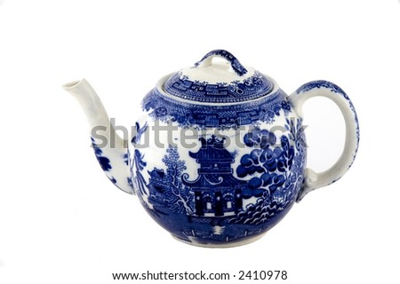 Small blue willow pattern tea pot with spout facing left and handle facing right