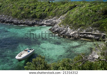 Small boat anchored in a tropical cove next to a small island. - stock photo