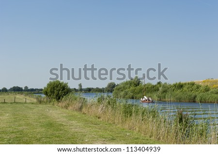 Small boat between the meadows in Holland leaving the harbor in Drachten through narrow ditch