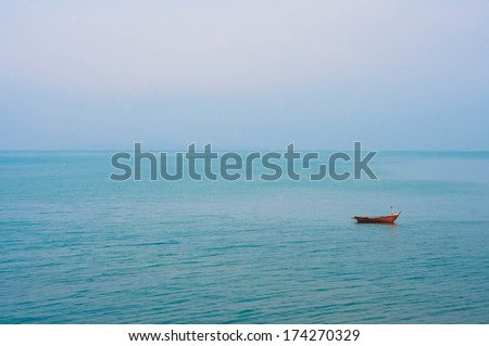 Small boat floating in the sea - stock photo