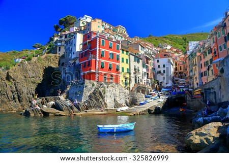 Small boat floating inside Riomaggiore harbor and colorful tower houses on the shore, Cinque Terre, Italy