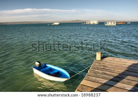 Small boat next to pier in sea lagoon. Shot in West Coast Nature Reserve, near Langebaan, Western Cape, South Africa.