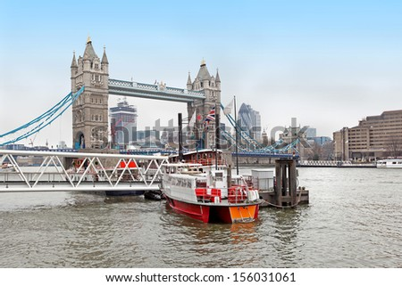 Small boat on Thames river with Tower bridge in background