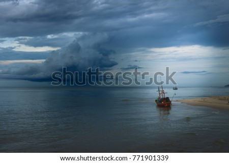 Small boat on the beach in thailand with the rain storm in background