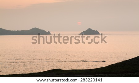Small boat races back to port by headland overlooking the coast at sunset at Port Quin, Cornwall, England, United Kingdom - stock photo