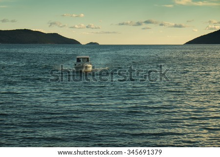 Small boat returning from the open sea at the afternoon - stock photo