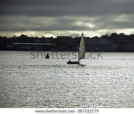Small boat sails across New Bedford harbor on a cloudy evening  - stock photo