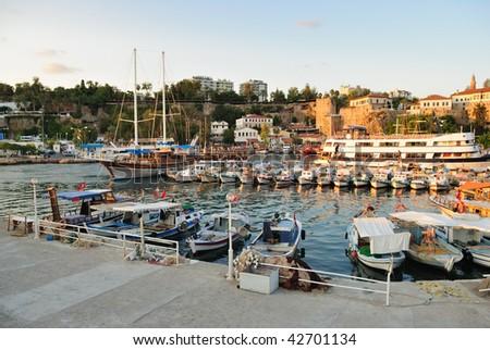Small boats and yacht in a Antalya harbor, Turkey - stock photo