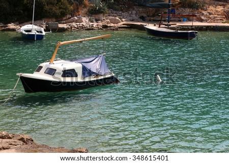 Small boats in clear blue sea. In town Vela Luka, on the Korcula island, Croatia. - stock photo