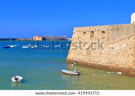 Small boats near the walls of Santa Catalina Castle in Cadiz, Andalusia, Spain - stock photo