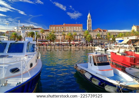 Small boats on the Adriatic sea coast with traditional buildings and Venetian church, Split, Croatia
