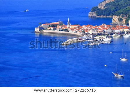 Small boats on the Adriatic sea near old harbor and town, Budva, Montenegro - stock photo