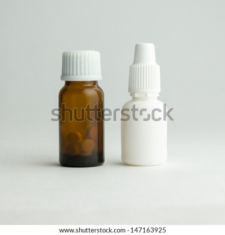 Small bottle from dark glass with a white cover and tablets.