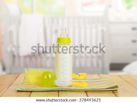 Small bottle with a nipple and milk, brush for washing dishes in the background - stock photo