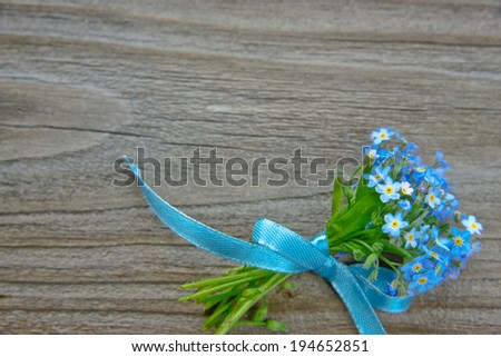 Small bouquet of blue forget-me-not, tied a blue ribbon, on the background of old wooden plank - stock photo