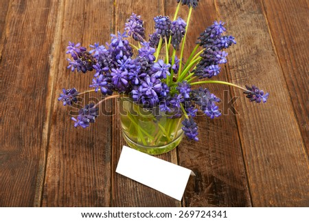 Small bouquet of hyacinth with a glass of water on the wooden table background - stock photo