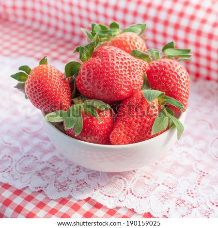 Small bowl filled with succulent juicy fresh ripe red strawberries on table with red checkered tablecloth and lace - stock photo