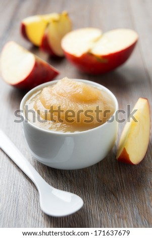 small bowl of apple puree with a fresh apple - stock photo