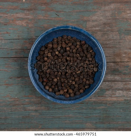 Small bowl of pepper corns, on a wooden table