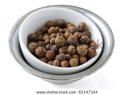 Small bowl with allspice and white background.