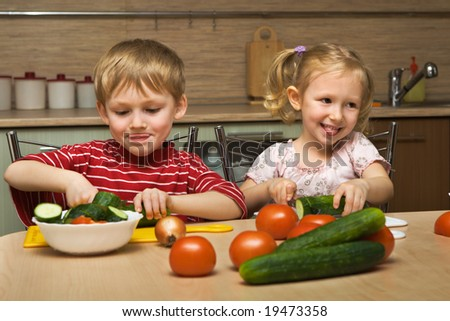 Small boy and girl cut vegetables - stock photo