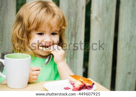 Small boy child with long blonde hair and serious face sitting at wooden table eating berry pie and biscuit with milk cup outdoor near wood fence - stock photo