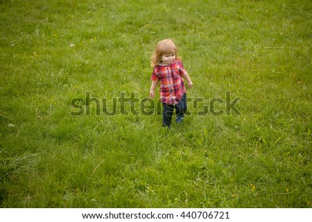 small boy child with long blonde hair in checkered shirt playing standing on green grass field outdoor on natural background, copy space