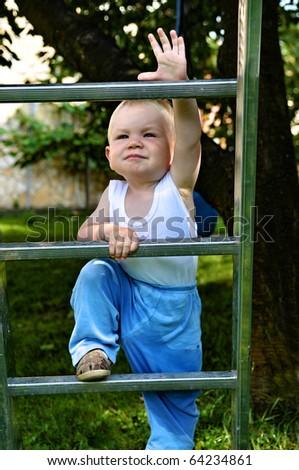Small boy climbing ladder - stock photo