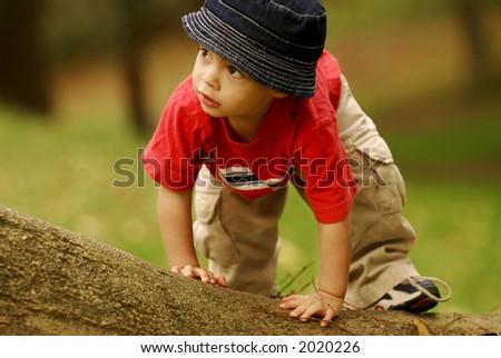 Small boy climbing over fallen tree. - stock photo