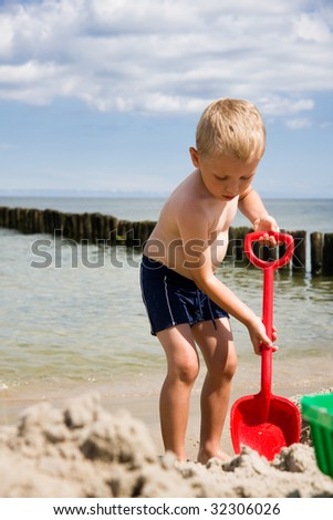 Small boy digging in sand on beach - stock photo