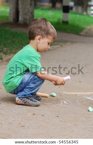 small boy drawing on the sidewalk with chalk - stock photo