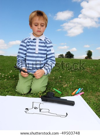 Small boy draws a picture of his toy gun