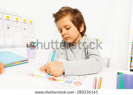 Small boy draws with pencil on the paper sitting - stock photo