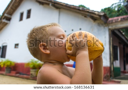 Small boy  drinking coconut milk - stock photo