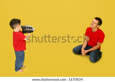 Small boy filming man with video camera.  Full body over yellow. - stock photo