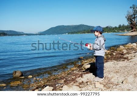Small boy fishing on lake - stock photo