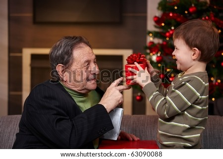 Small boy giving present to grandfather at christmas, smiling. ? - stock photo