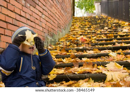 Small boy goofing around in autumn scenery - stock photo