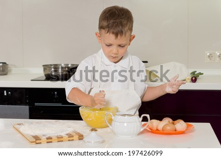 Small boy in a white apron doing the baking in the kitchen adding ingredients to the mixing bowl as he makes his favorite cake - stock photo