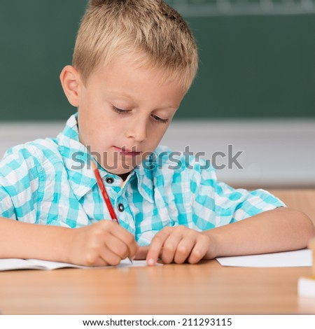 Small boy in class writing notes concentrating as he writes in his copybook with a pencil, close up view at a desk - stock photo