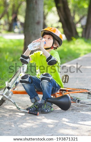 Small boy in green jacket drinks water from plastic bottle and sits on cycle on alley in city park - stock photo