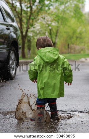 small boy in green raincoat playing in puddles - stock photo