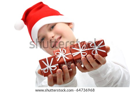 Small boy in Santa's red hat holding Christmas presents isolated on white
